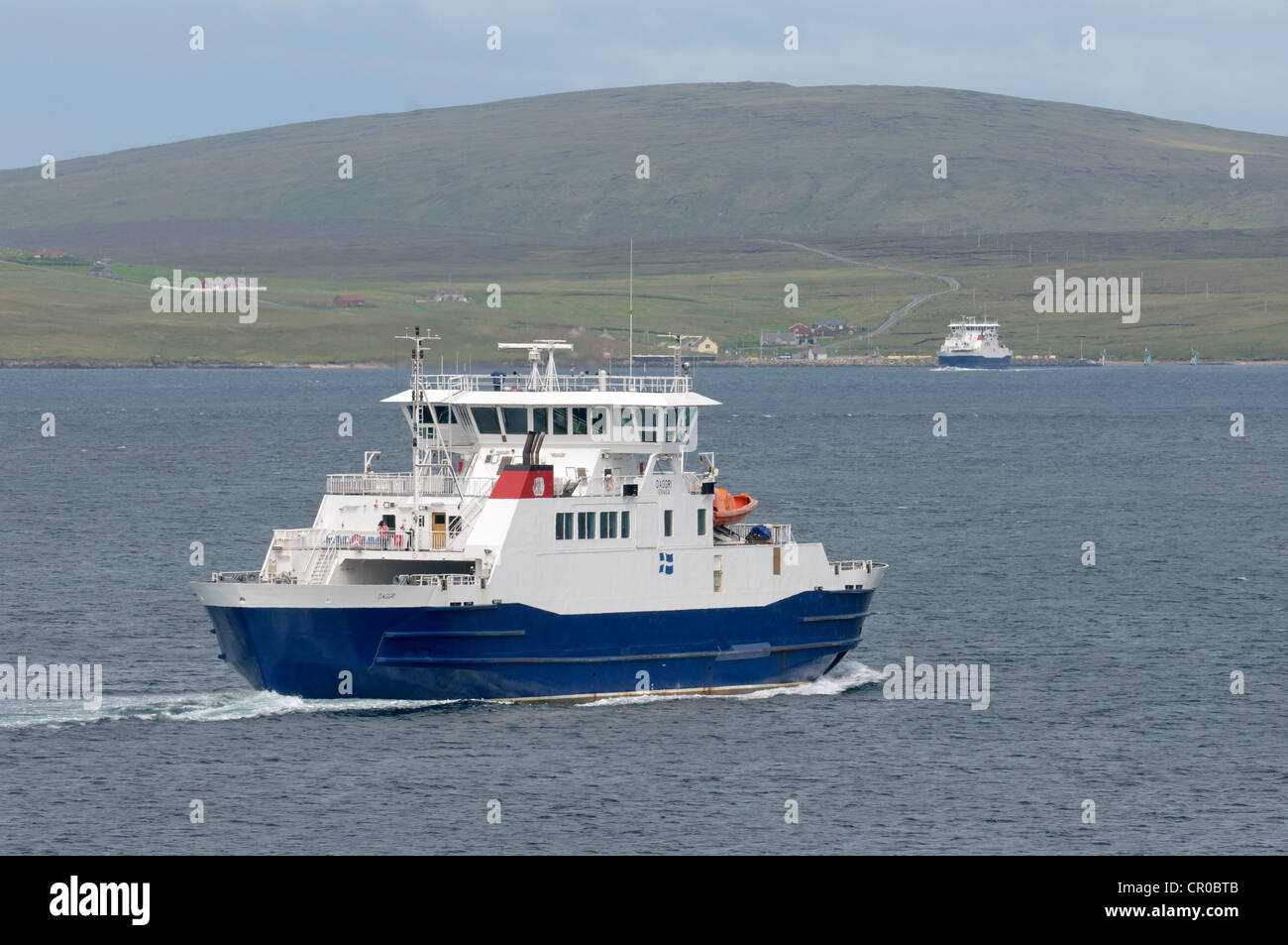 Ferries crossing Yell Sound in the Shetland Isles. Ferry 'Daggri' in foreground. Village of Ulsta and isle - Stock Image