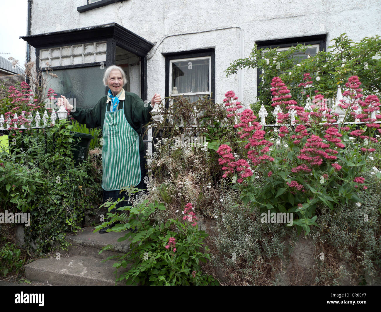 An elderly woman outside her cottage in Hay-on-Wye during the Hay book Festival in Wales UK    KATHY DEWITT - Stock Image