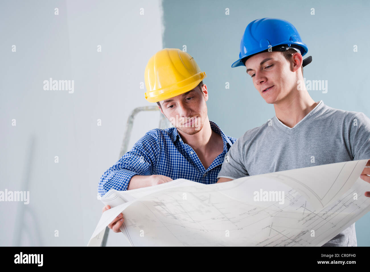 Two young tradesmen looking at a building plan - Stock Image