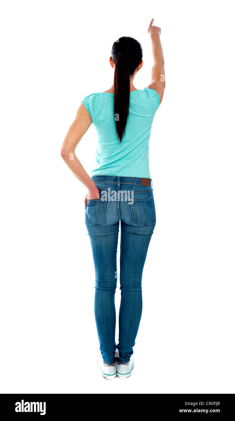 Rear view of young woman in casuals pointing at copyspace - Stock Image