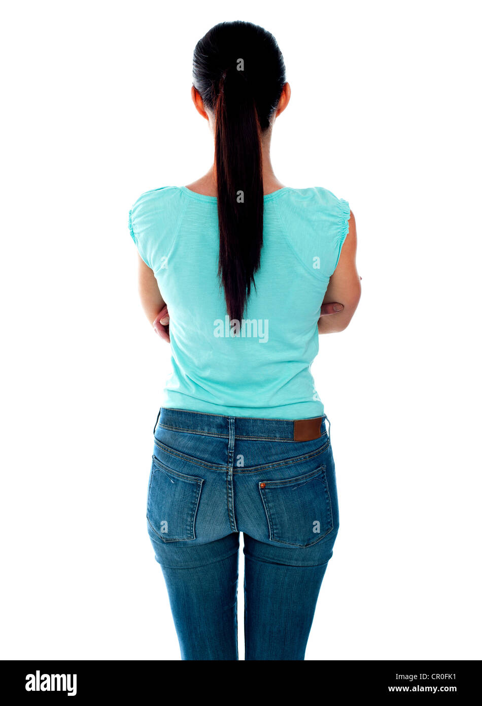 Beautiful young woman looking at wall. Rear view. Isolated over white. - Stock Image