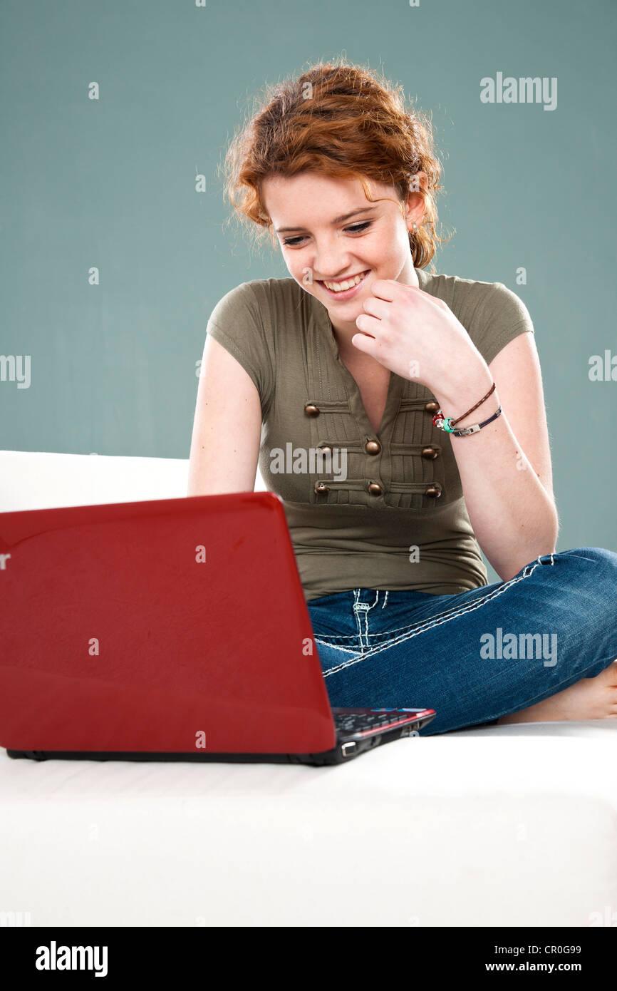 Smiling girl using a laptop - Stock Image