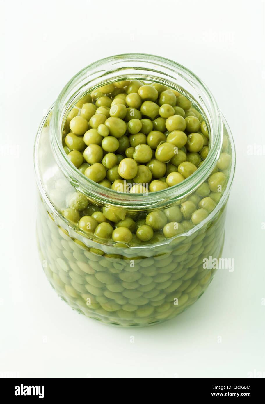 Opened jar of preserved green peas - Stock Image