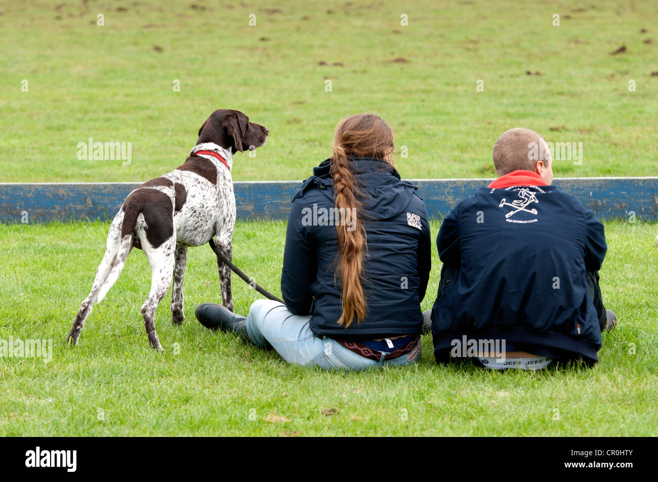 Two students with German Pointer dog watching a polo match - Stock Image