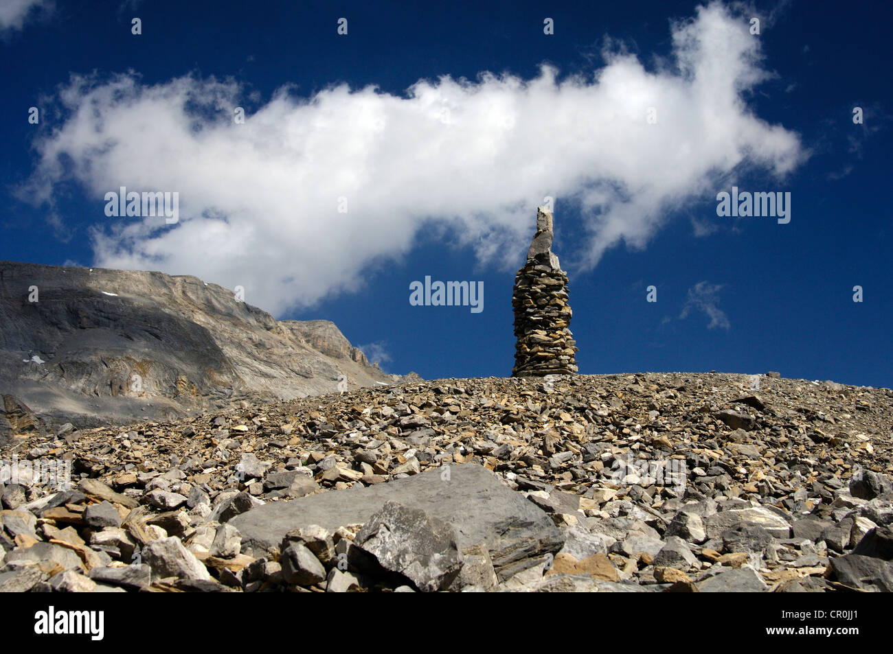 Cairn as signpost and orientation help in rocky alpine terrain without trails, Valais, Switzerland, Europe - Stock Image