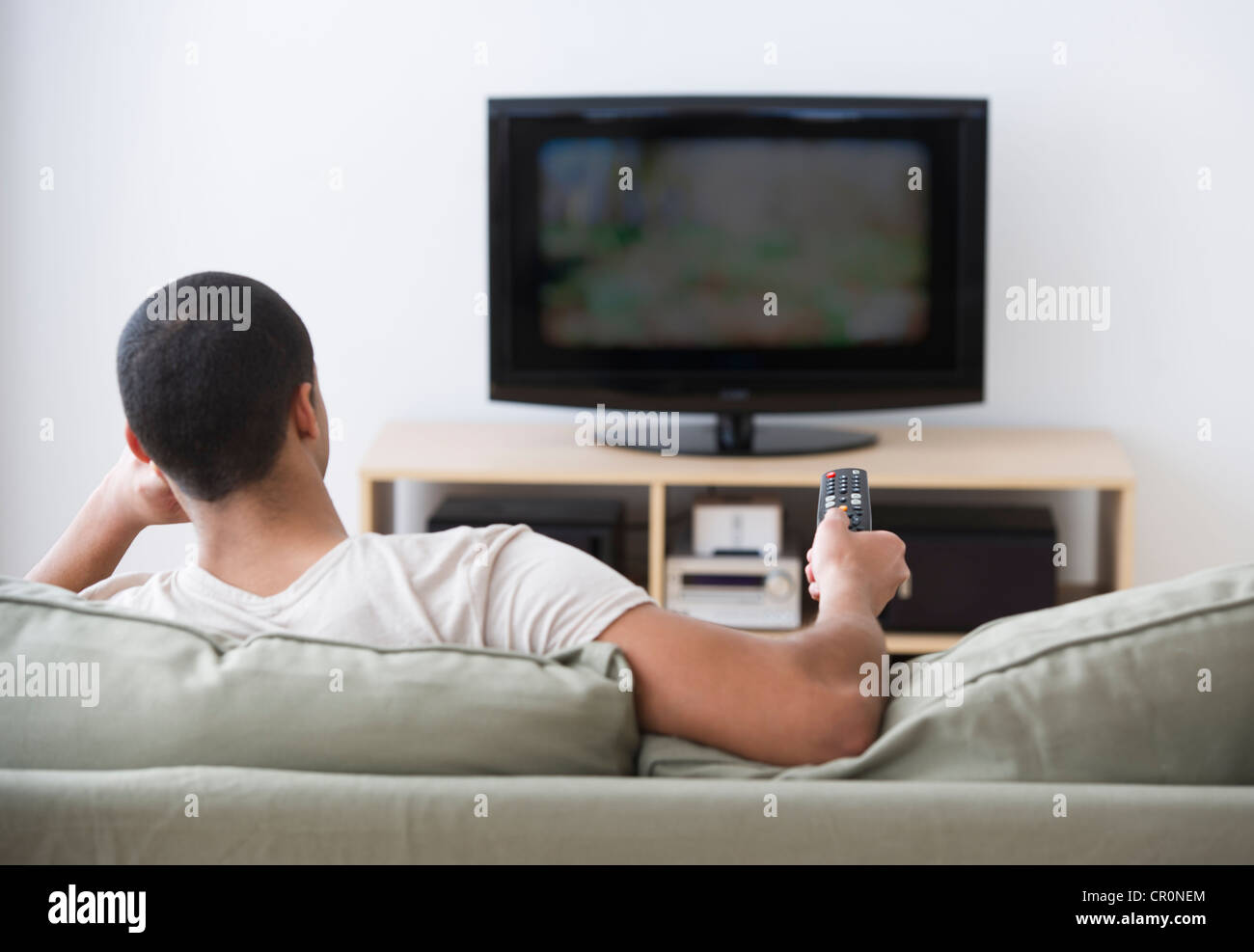USA, New Jersey, Jersey City, Man watching tv at home - Stock Image