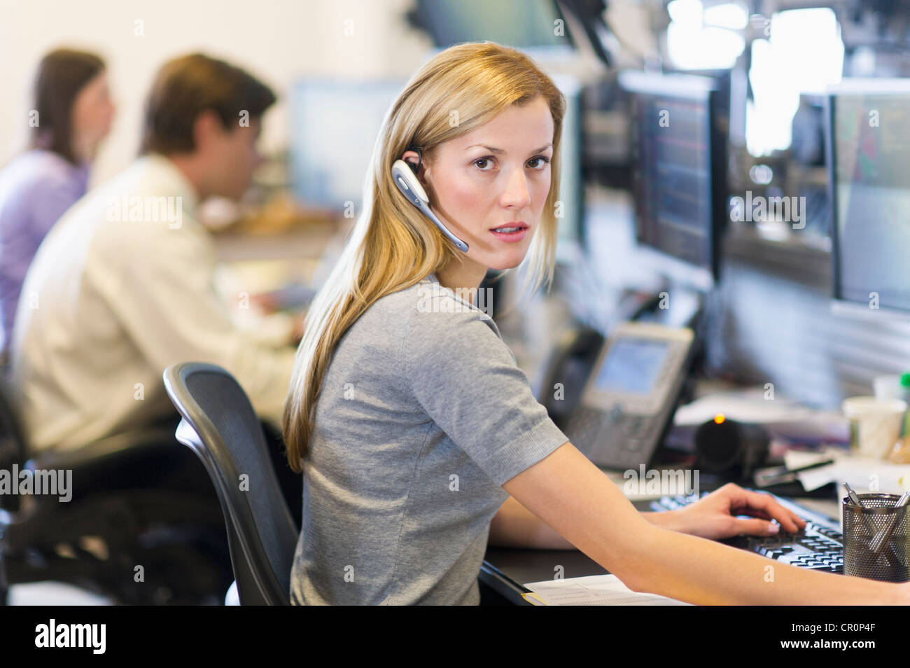 USA, New York, New York City, Portrait of female trader at trading desk Stock Photo