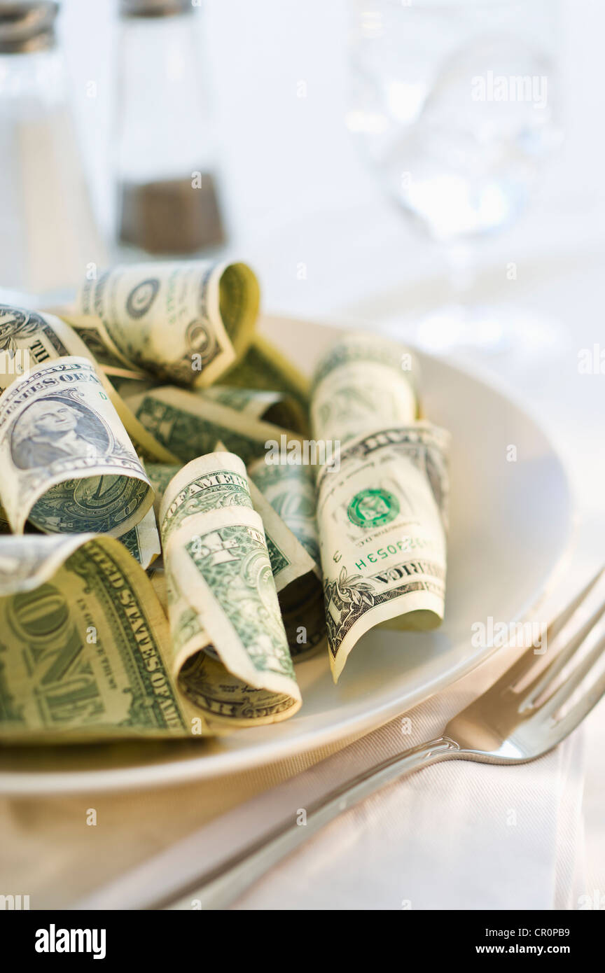 Paper currency on dinner plate, studio shot Stock Photo