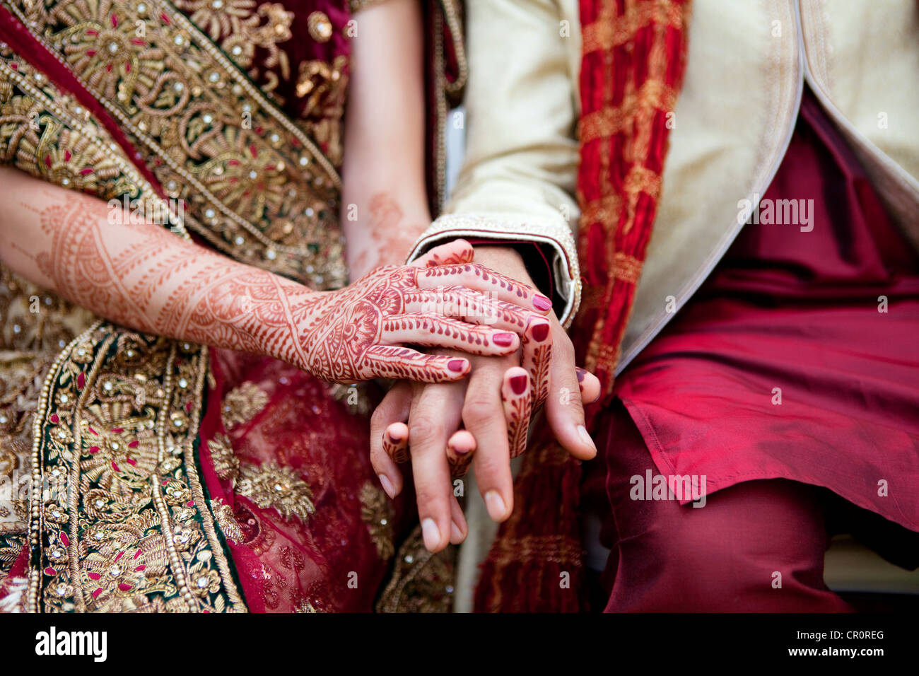 Bride and groom in traditional Indian wedding clothing with henna tattoos Stock Photo