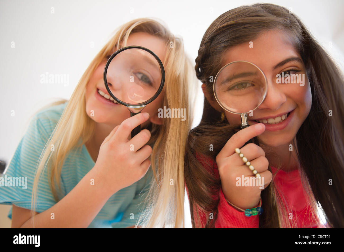 USA, New Jersey, Jersey City,  Two girls looking through magnifying glasses Stock Photo