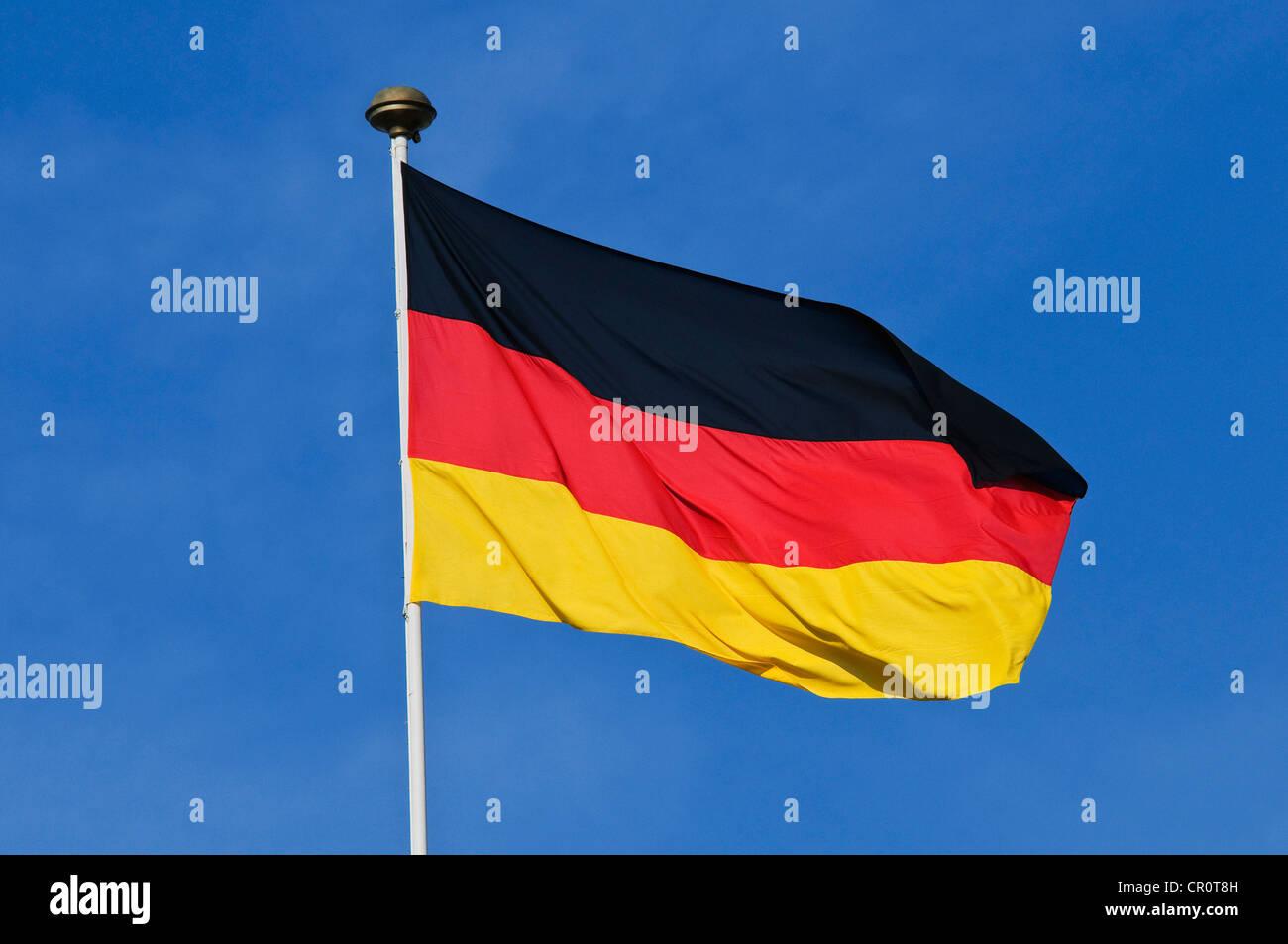 German national flag against blue sky - Stock Image
