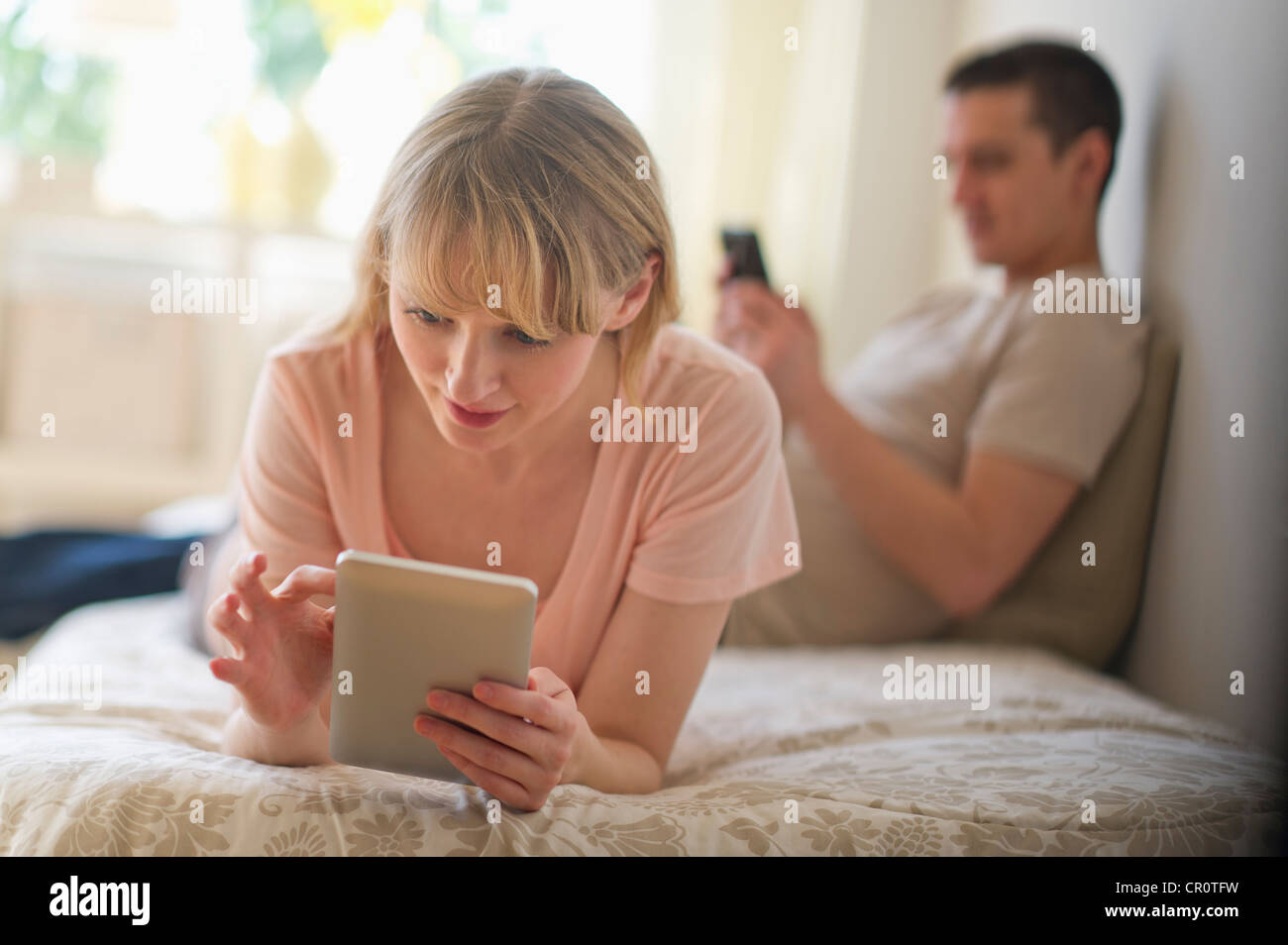 USA, New Jersey, Jersey City, Couple lying on bed and using digital devices - Stock Image