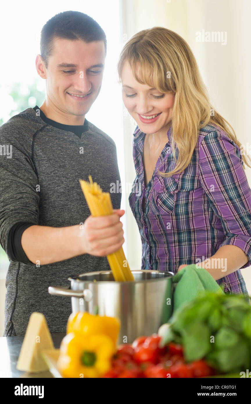 USA, New Jersey, Jersey City, Couple cooking together - Stock Image