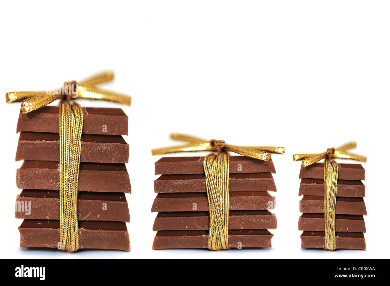 Three stacks of chocolate tied with ribbons - Stock Image