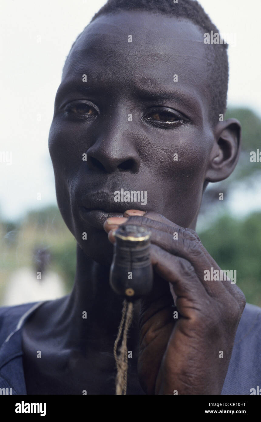 A Dinka man smokes a traditional tobacco pipe - Stock Image