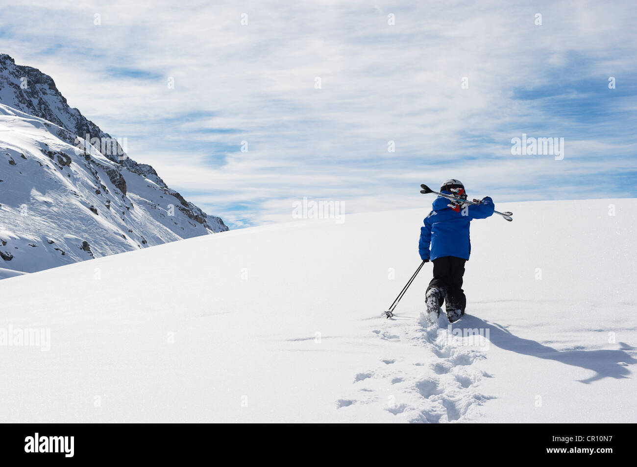 Child carrying skis up snowy mountain - Stock Image