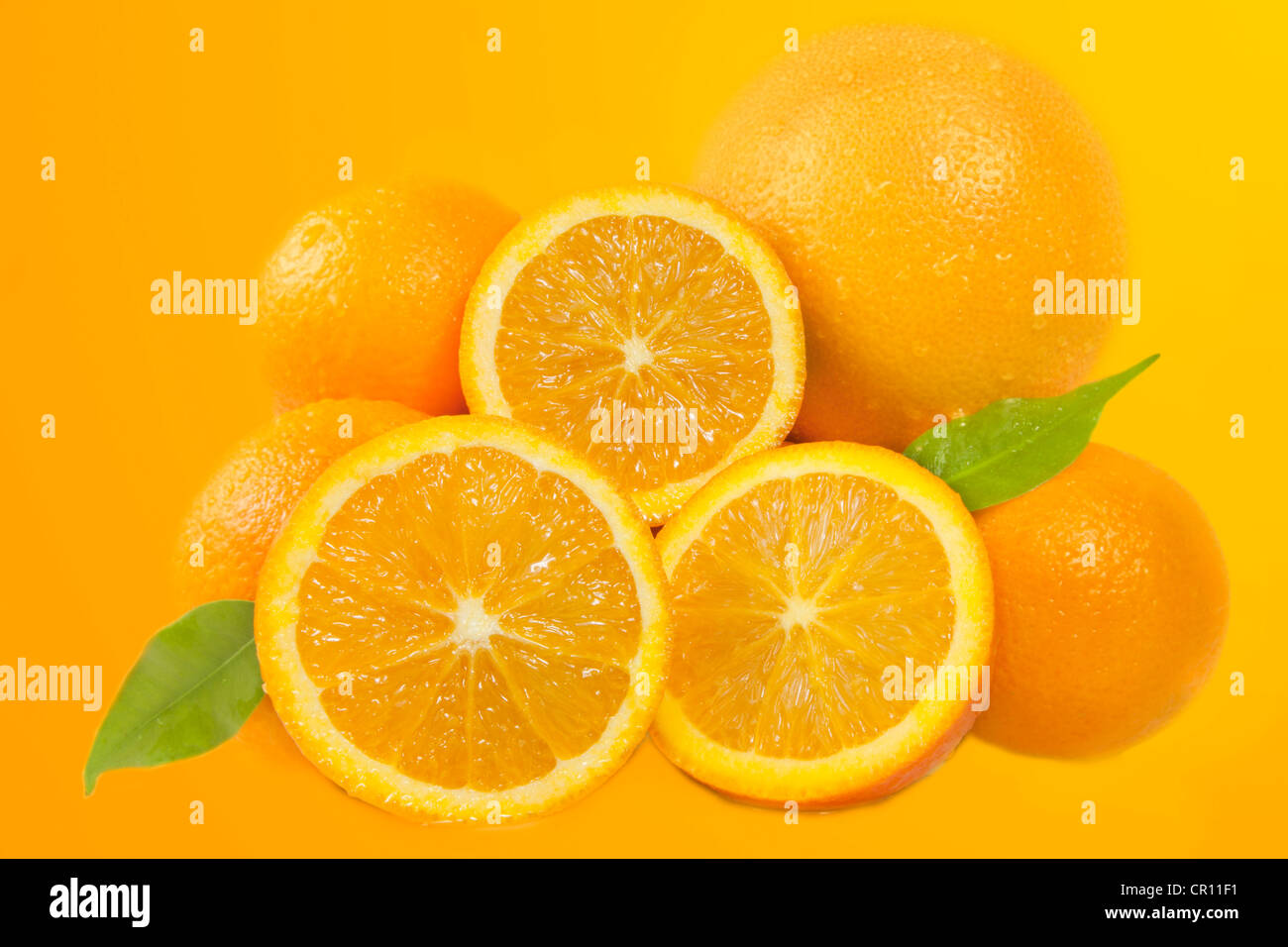 Composition of fresh oranges with green leaves background - Stock Image