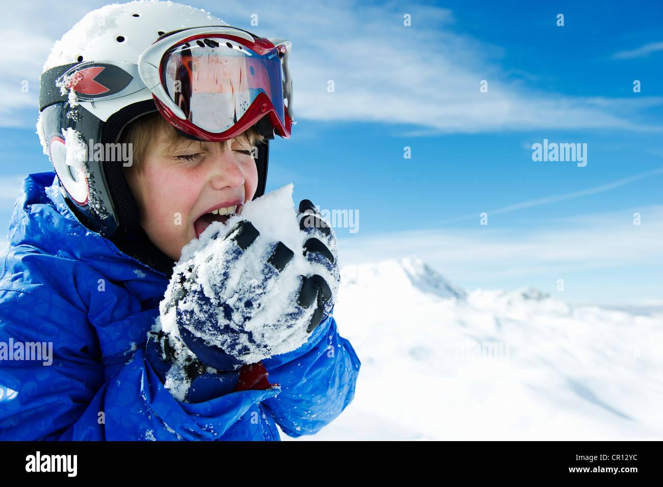 Boy tasting snowball on mountain - Stock Image