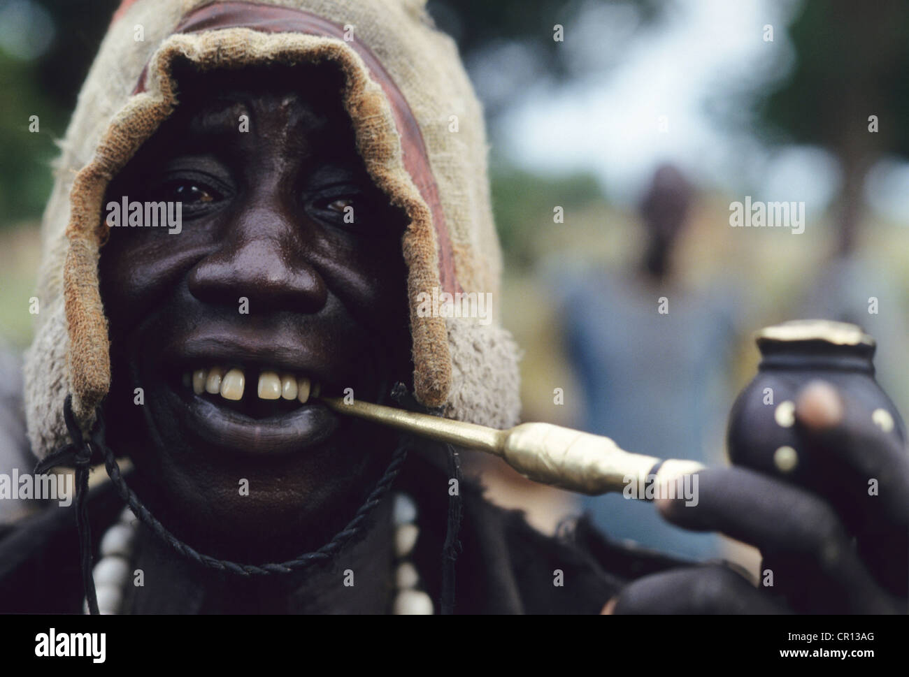 A Dinka man smokes a traditional tobacco pipe in the triple A camp of Atepi - Stock Image