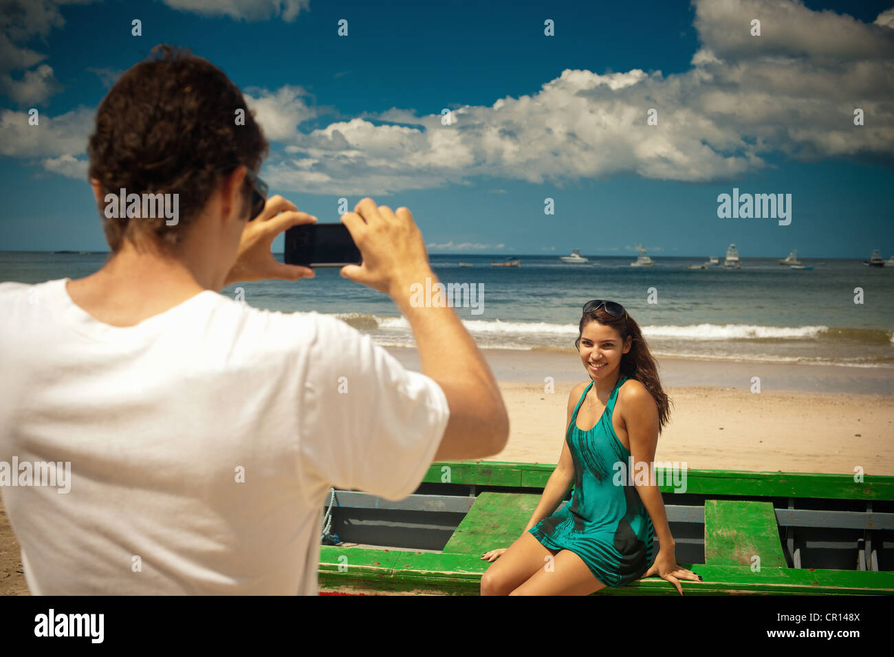 Man taking picture of girlfriend - Stock Image
