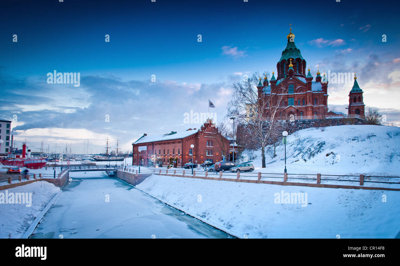Snow-covered castle by frozen river - Stock Image