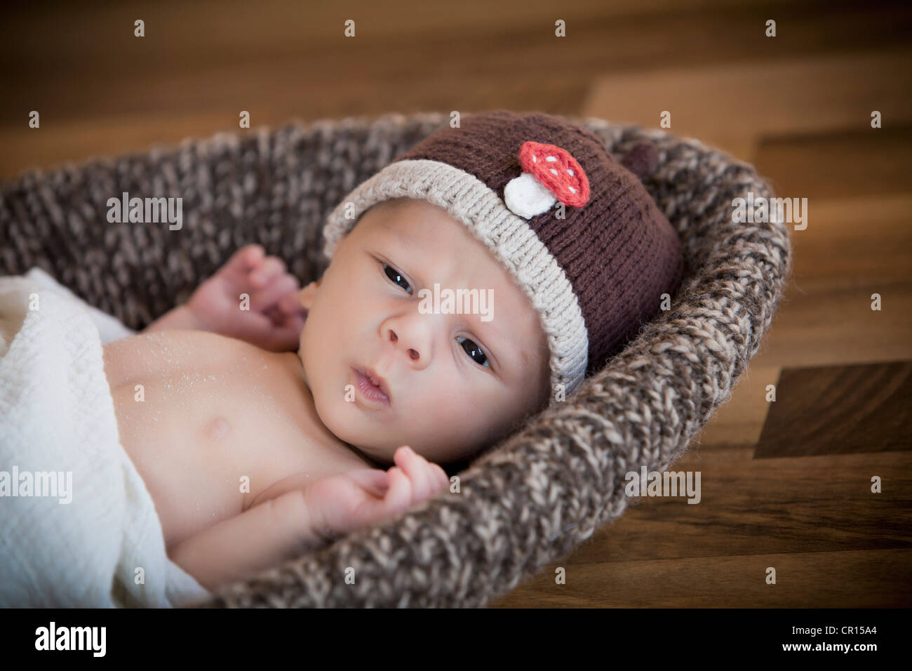 Newborn baby 3 weeks wearing a hat lying in a basket