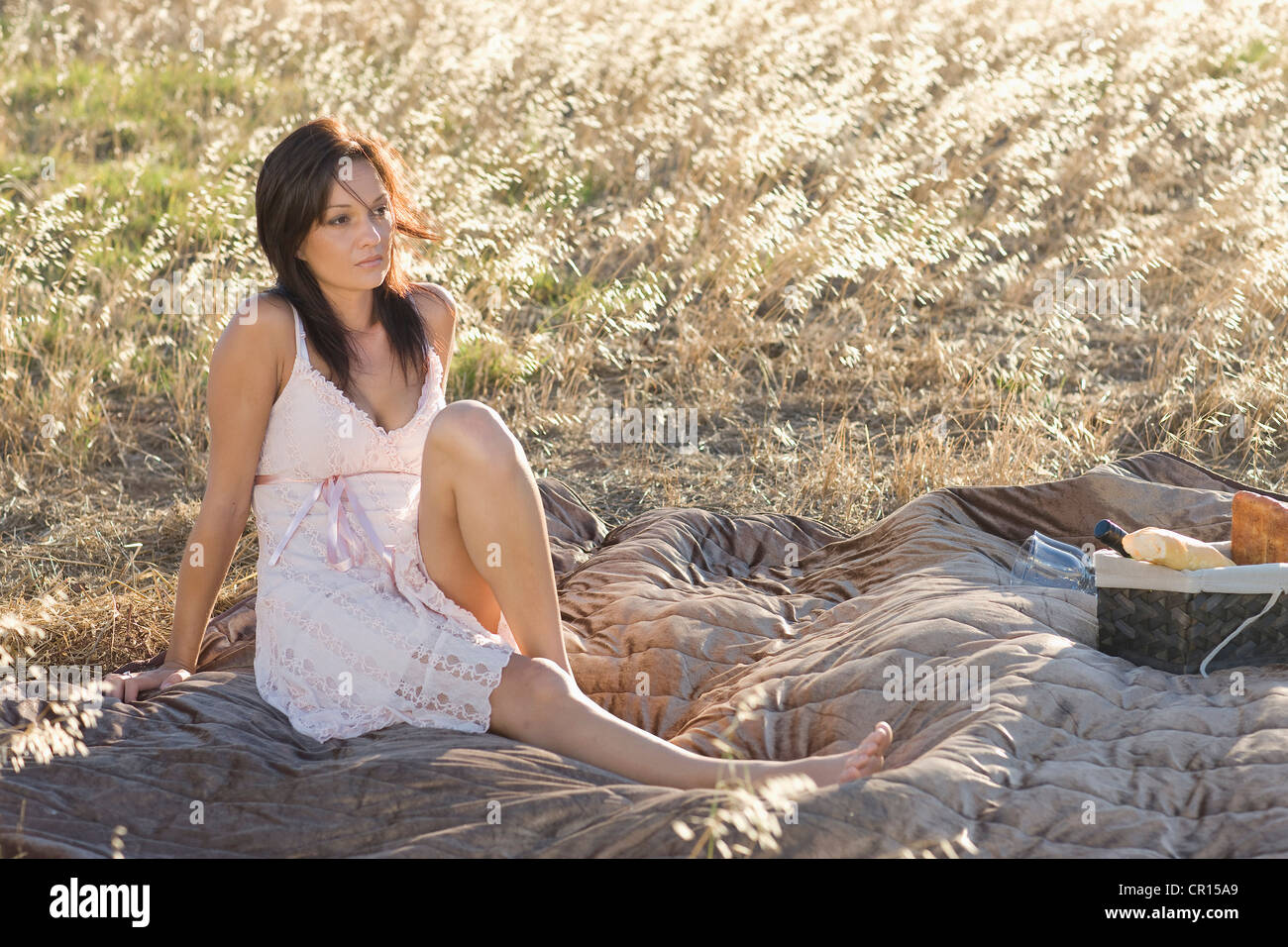 Woman picnicking in wheatfield - Stock Image
