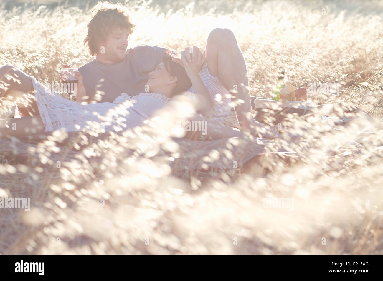 Couple picnicking in wheatfield - Stock Image