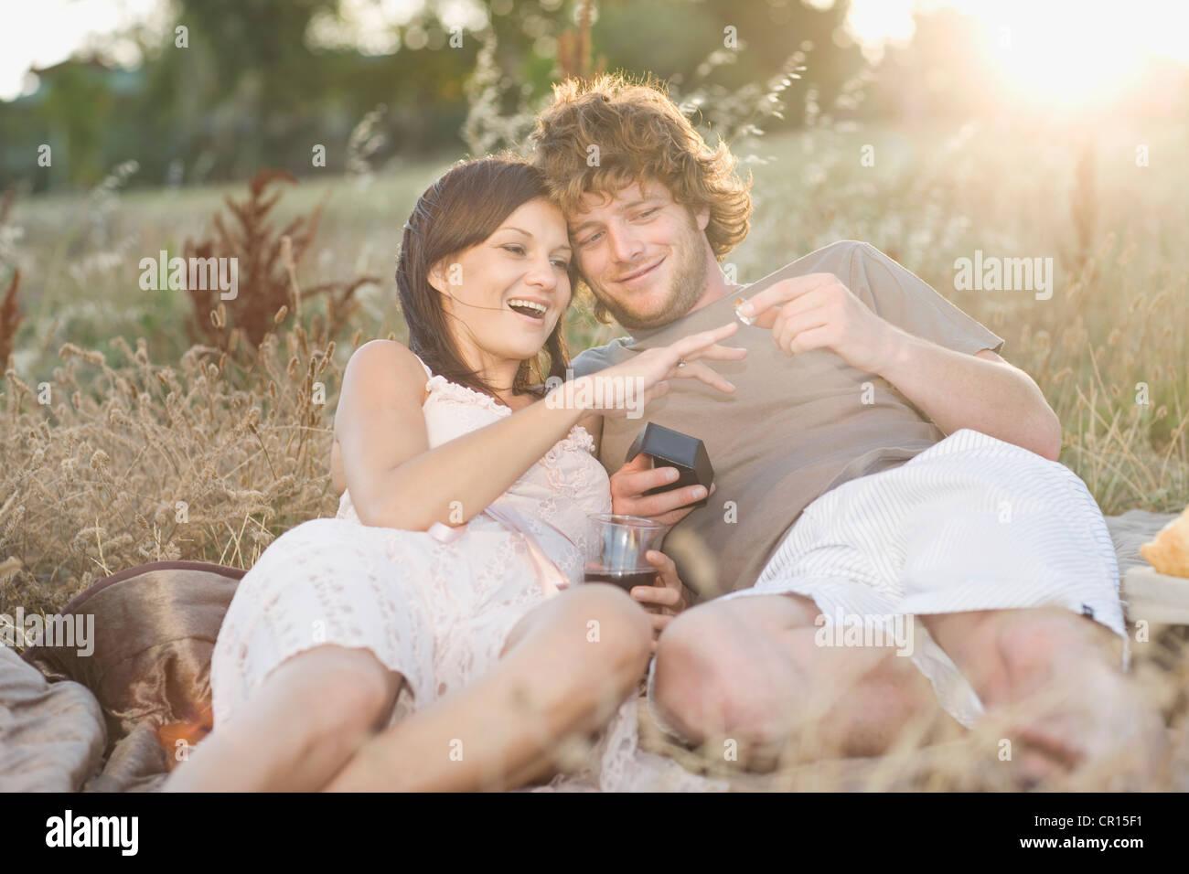 Man proposing to girlfriend at picnic - Stock Image