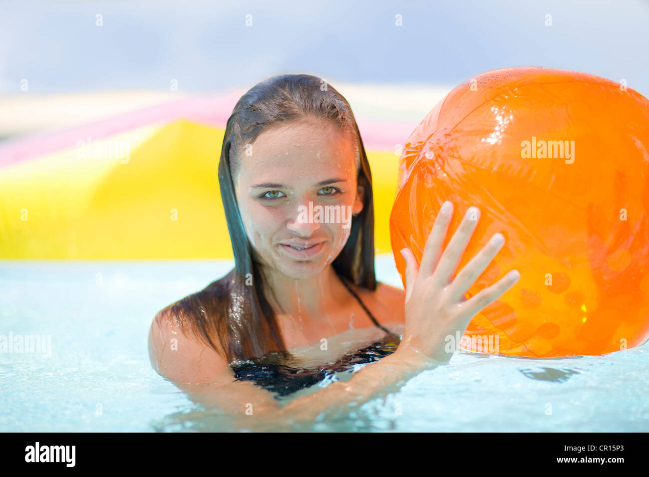 Girl holding inflatable toys in pool Stock Photo