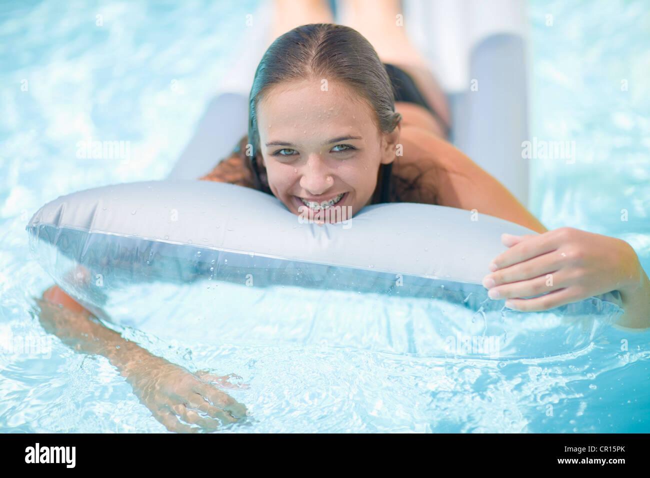 Teenage girl in braces relaxing in pool - Stock Image