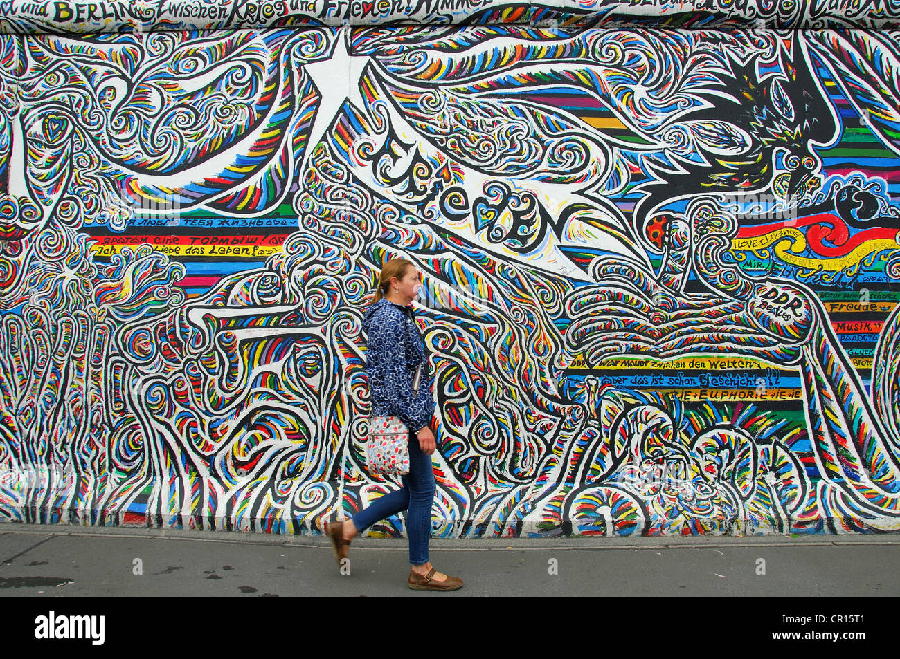 BERLIN, GERMANY. A woman walking past a mural at the East Side Gallery, a section of the Berlin Wall decorated by Stock Photo