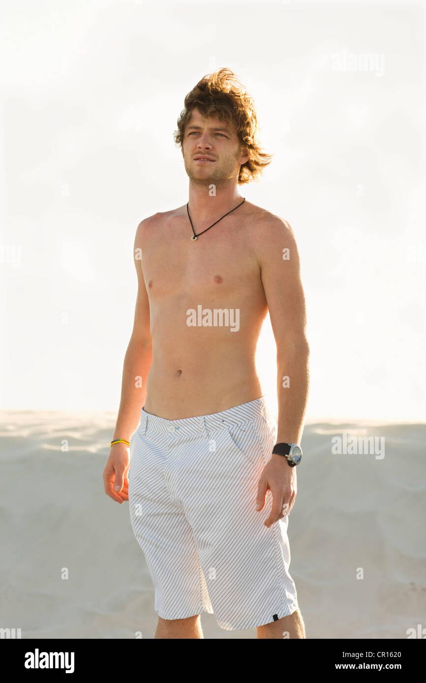 Man wearing shorts on beach - Stock Image