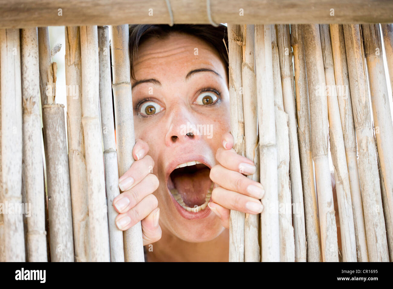 Close up of woman gasping behind fence - Stock Image