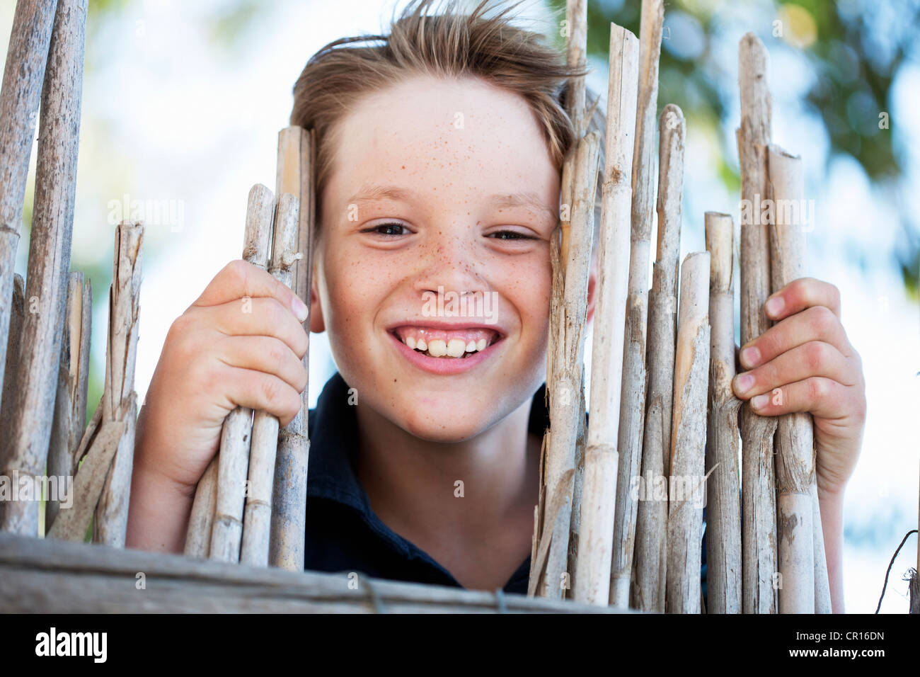 Close up of boy smiling behind fence - Stock Image