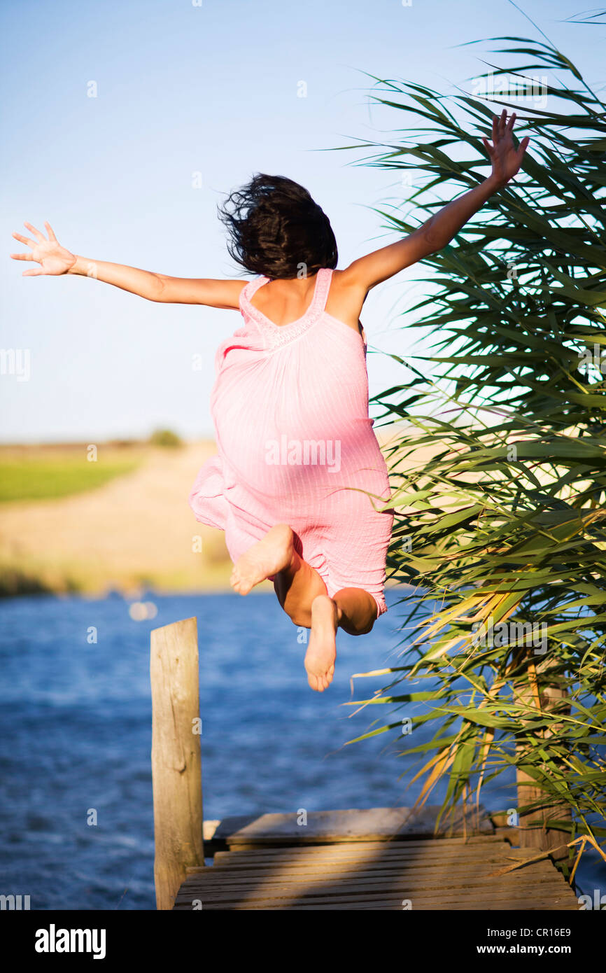 Woman jumping off dock into lake Stock Photo