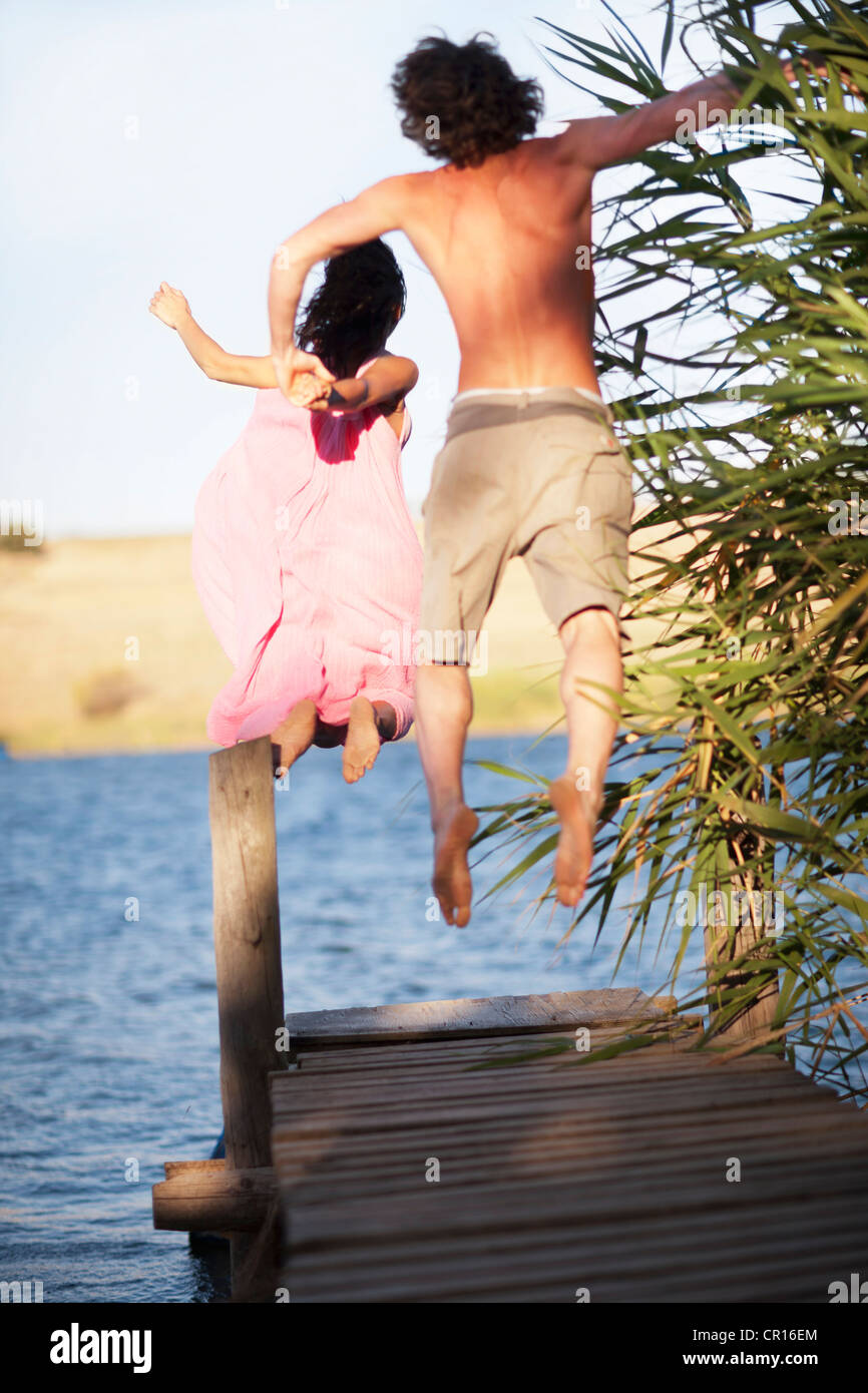 Couple jumping off dock into lake Stock Photo