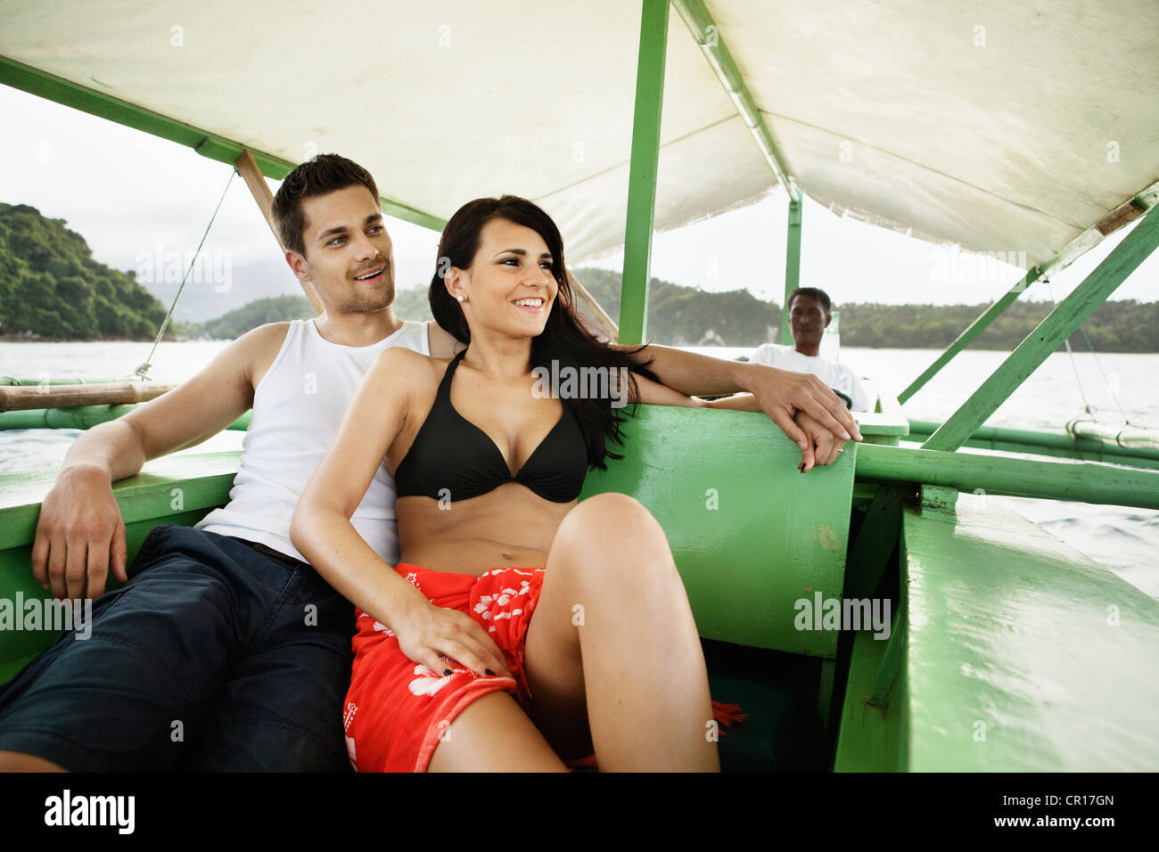 Couple relaxing on boat in river Stock Photo