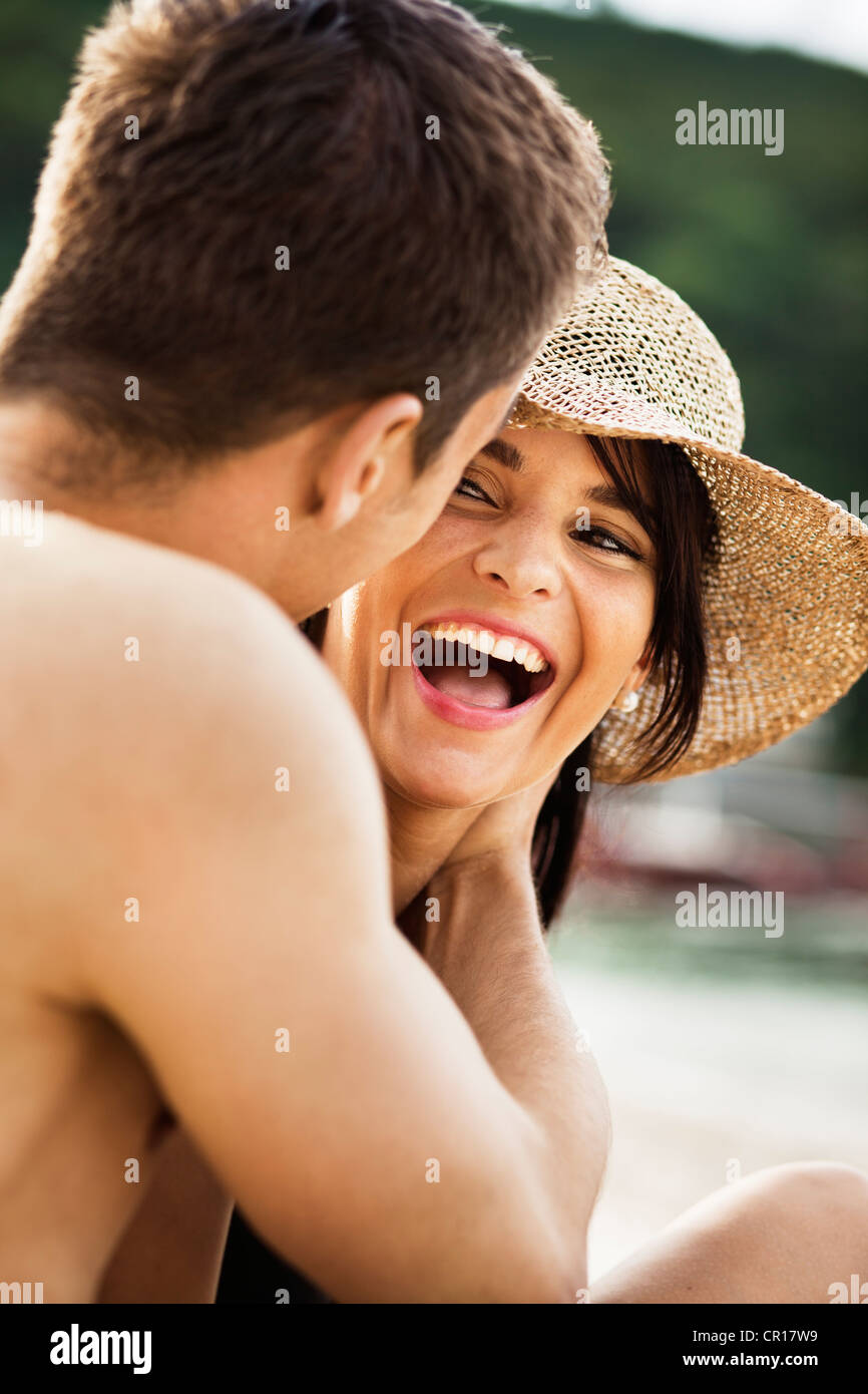Couple laughing on beach - Stock Image