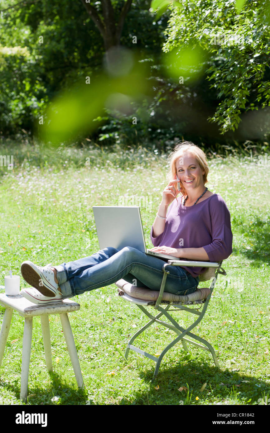 Smiling woman using laptop outdoors - Stock Image