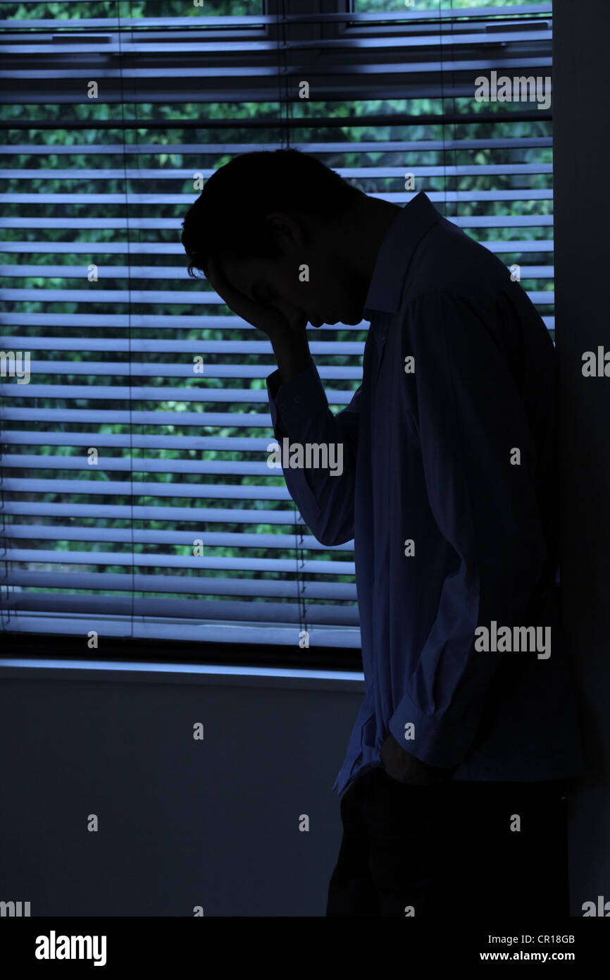 Silhouette of young male leaning against a wall by a window. - Stock Image