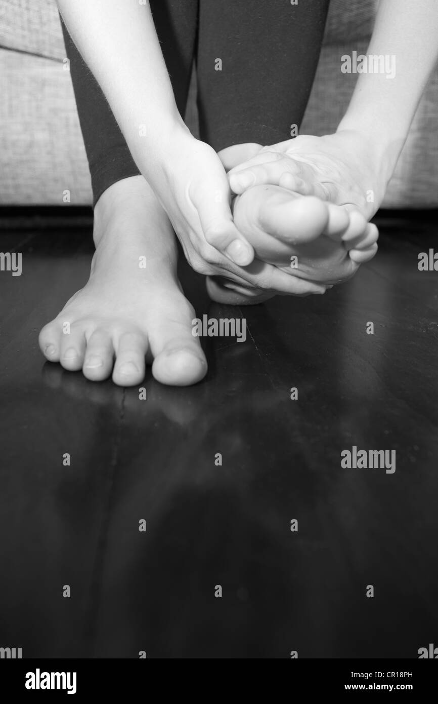 A young woman rubs her aching feet on the sofa. Stock Photo