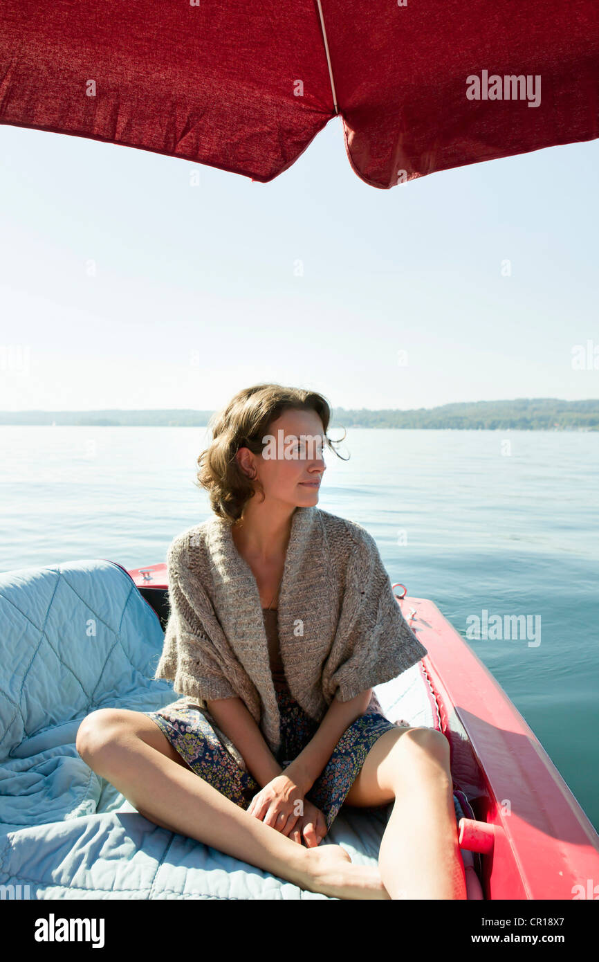 Woman relaxing in boat on still lake Stock Photo
