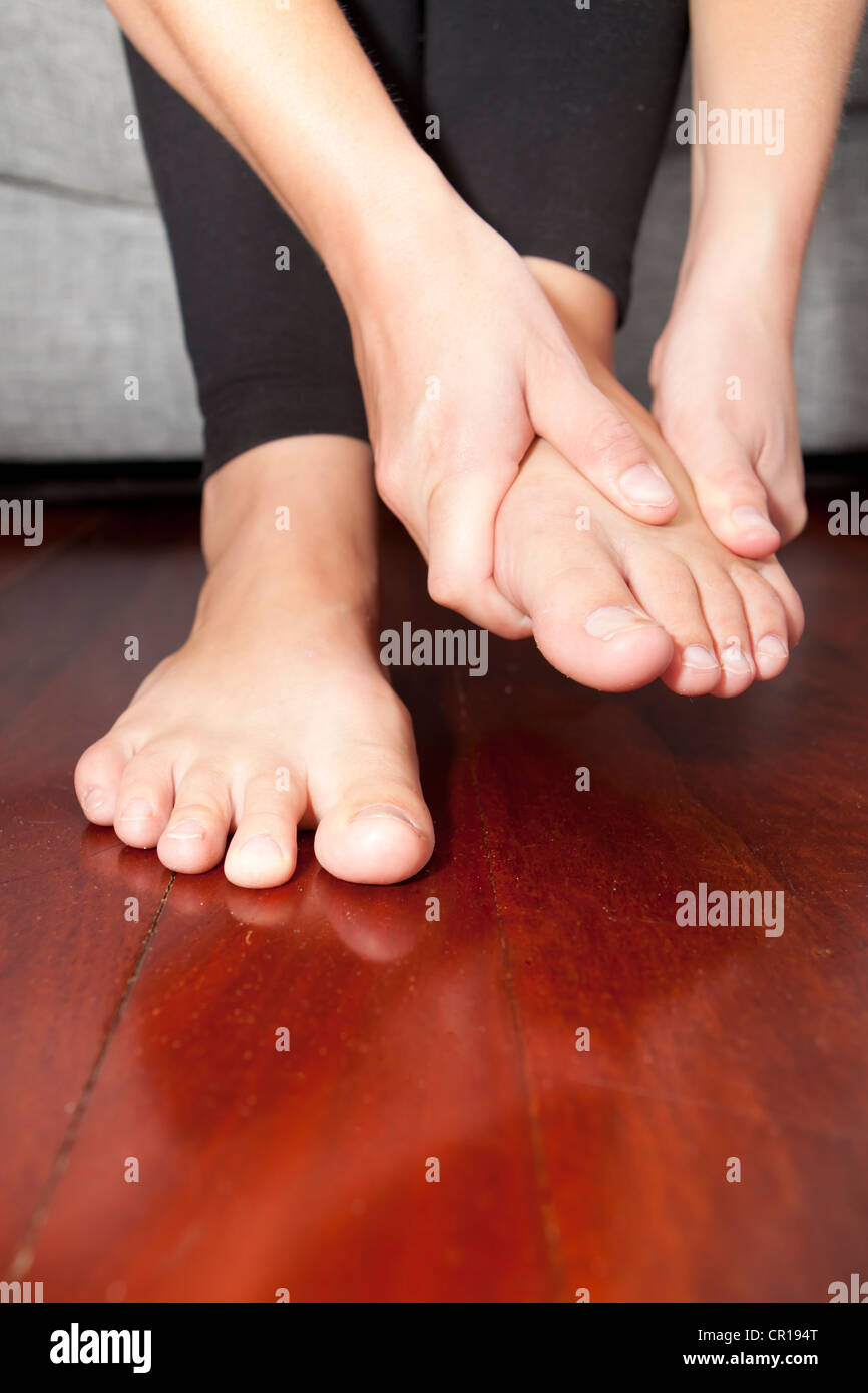 A young woman rubs her aching feet on the sofa. - Stock Image