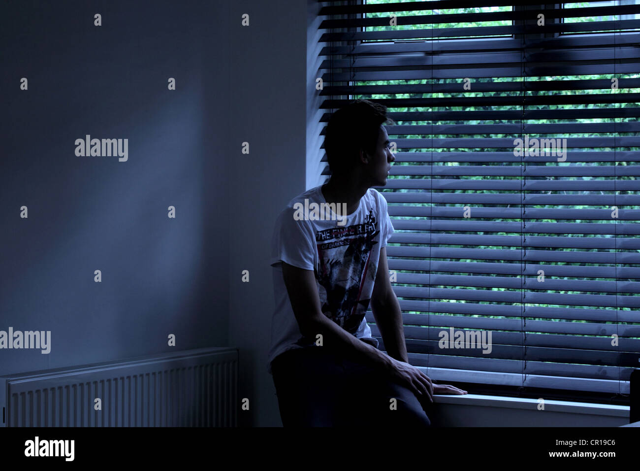 Young male sitting in a dark room looking out through a window blind. Model and property (owned by photographer) - Stock Image
