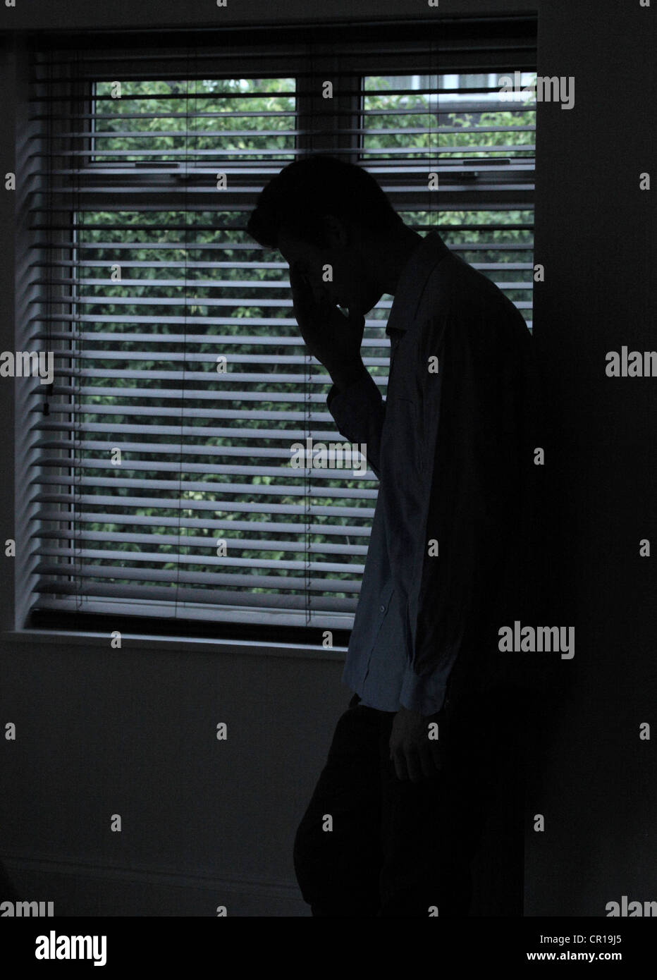 Silhouette of a male standing in a dark room with light from a window with blinds showing his shape, hand to face. - Stock Image