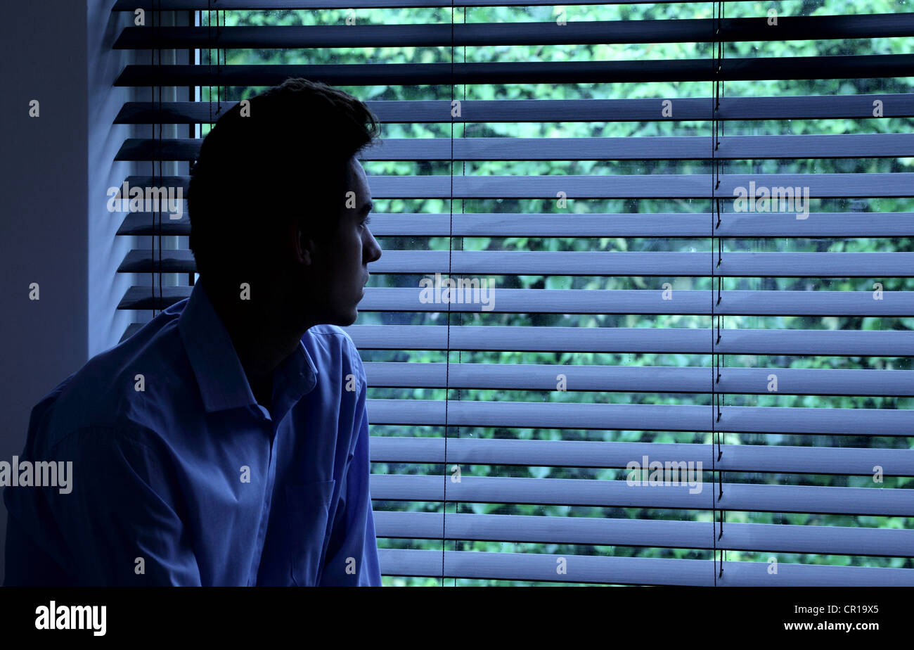 Young man sitting in a dark room looking out through a window blind. - Stock Image