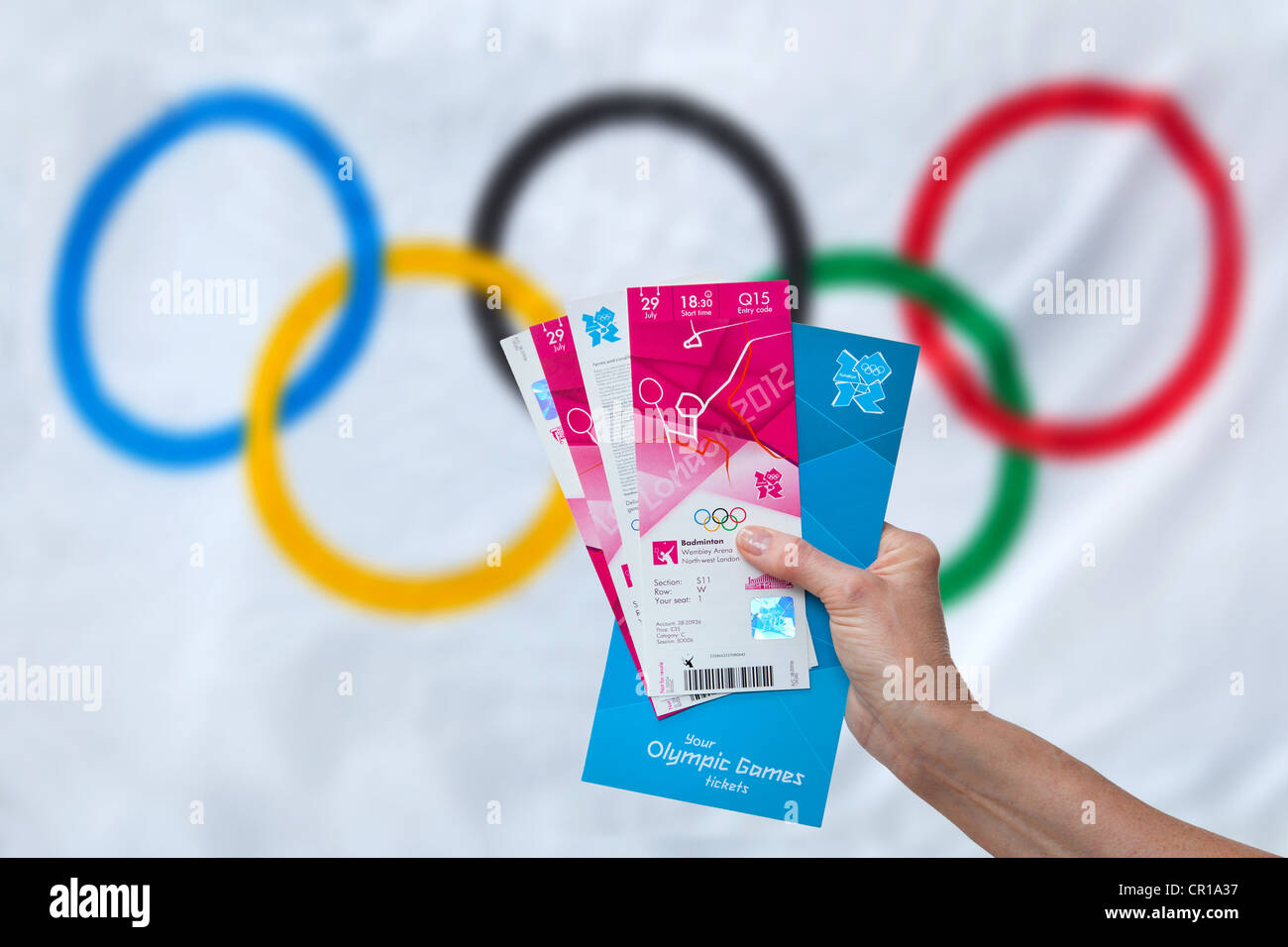 Person holding their Olympic tickets for the London 2012 Games with the Olympic flag in background - Stock Image