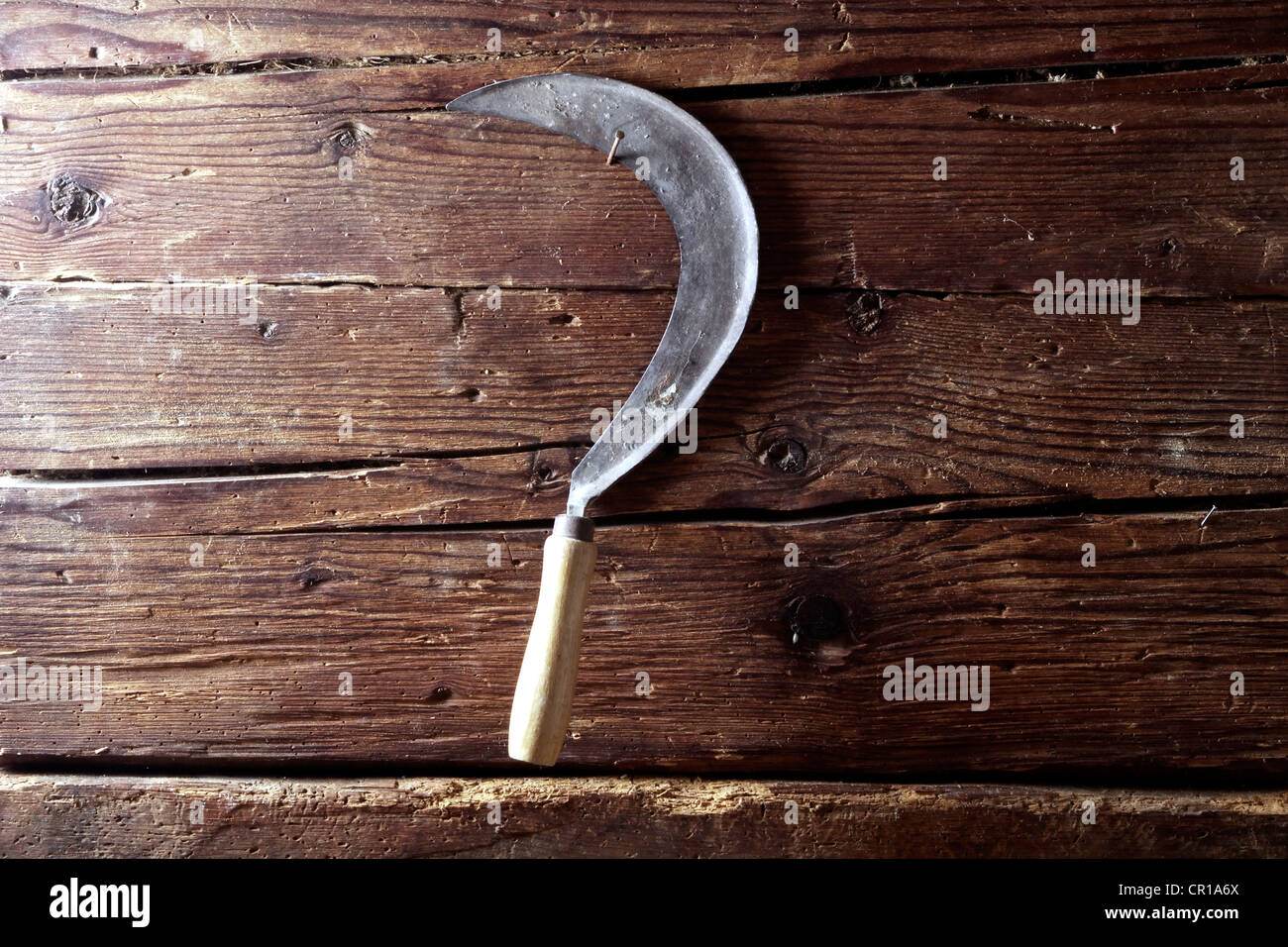 Old sickle hanging on a rustic wooden wall - Stock Image