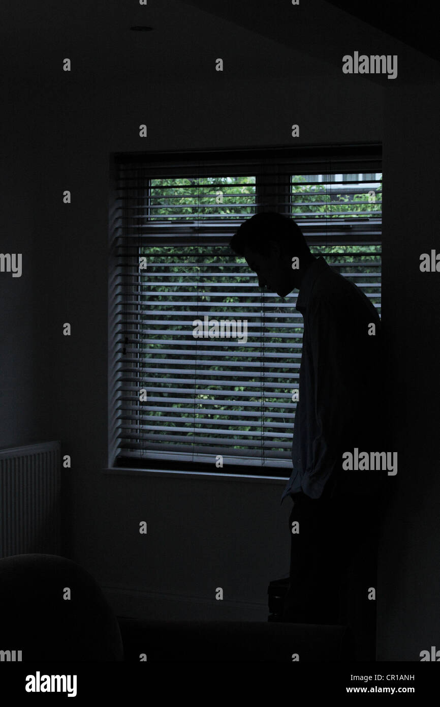 Silhouette of a male standing in a dark room with light from a window with blinds showing his shape. - Stock Image